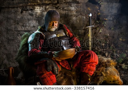 Old medieval King in armor with dish is sitting on furs near the camp fire and having a lunch - stock photo
