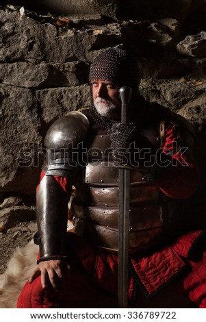 Old medieval King in armor with sword is sitting on furs - stock photo