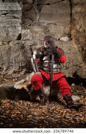 Old medieval King in armor with sword on the rocks background. - stock photo