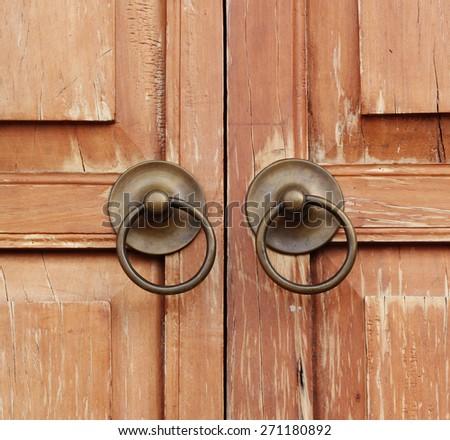 Old medieval metal handles on antique wooden door - stock photo