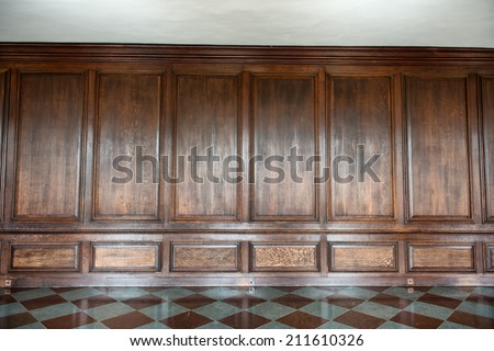 Old medieval wood paneling covering a wall in a historical country house with a diamond pattern marble floor, background image with nobody - stock photo