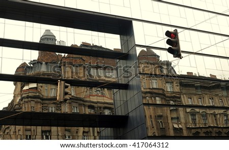 Old meets new: Glass reflection of old house - stock photo