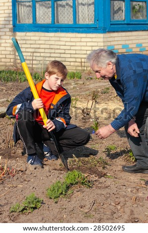 old men and boy with spade - stock photo