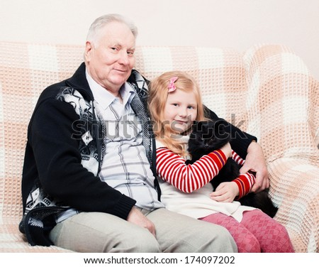 old men and little girl with cat - stock photo