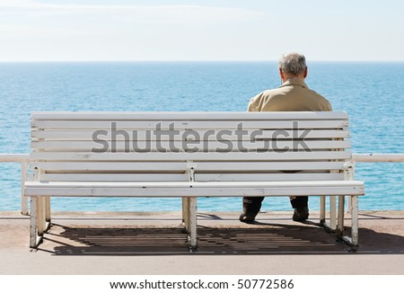 Old men sitting on the bench by the sea. - stock photo