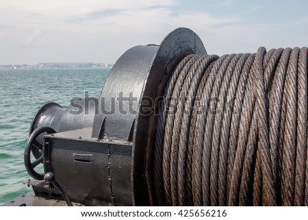 Old metal cable oiled marine winch on the ship on the background of the sea. Steel rope in the sea close-up lubrication. Textural background ship metal cable on a pulley and hired a crane - stock photo