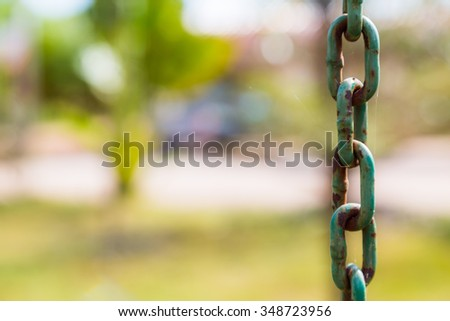 Old Metal Chains with rust on green background - stock photo