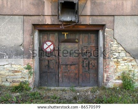 old metal door and old dirty cracked wall - stock photo