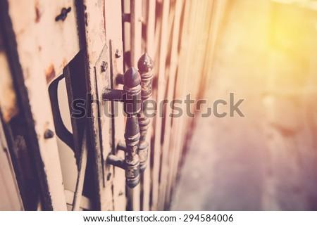Old metal door handle bar. Vintage filter - stock photo