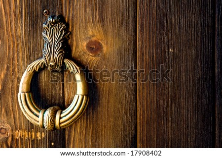 Old metal door handle knocker on a rough wooden background - stock photo