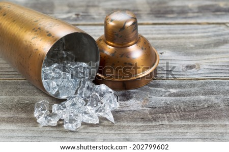 Old metal drink mixer lying on side with crushed ice flowing out onto rustic wood - stock photo