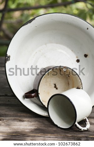 old metal enamel kitchenware at table, outdoor