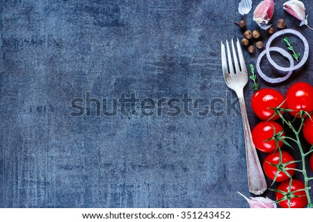 Old metal fork and ingredients (tomatoes, onion, garlic) on dark vintage background with space for text. Healthy food. Vegetarian eating. Fresh harvest from the garden. Top view. Rustic style. - stock photo