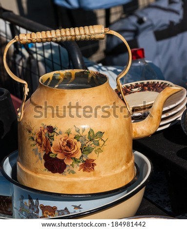 Old metal kettle decorated with roses and other dishes at at the flea market  in Jaffa (Israel). - stock photo