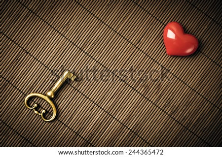 Old metal key and red heart on the brown mat - stock photo