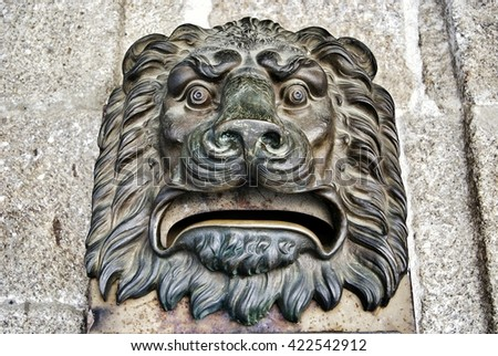 Old metal lion face postbox