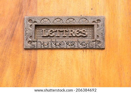 Old metal mailbox on the door decorated with plant motifs, Alsace, France - stock photo
