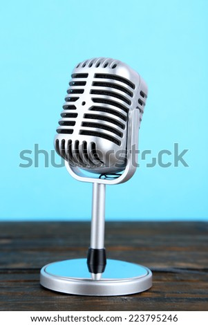 Old metal microphone on wooden table on light blue background - stock photo