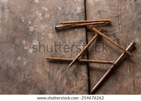 old metal nails put on dirty wood background - stock photo