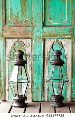 Old metal outdoor candle lamp stands on wood floor near mint wooden vintage background - stock photo