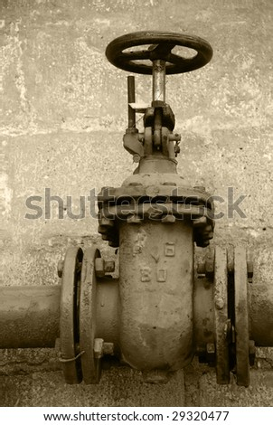 old metal pipe and hand valve. Sepia