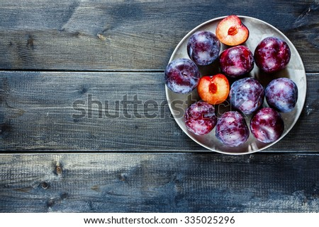 Old metal plate with plums over dark board. Top view. Fruits background with space for text. Agriculture, Gardening, Harvest Concept. - stock photo