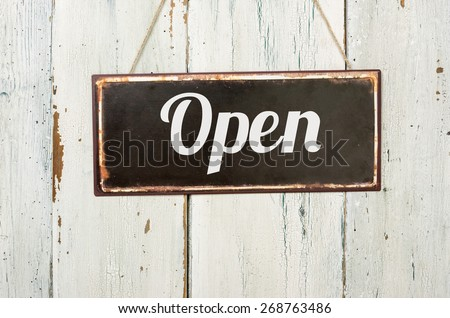Old metal sign in front of a white wooden wall - Open - stock photo
