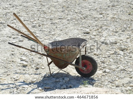 Old metal wheelbarrow on gravel used for cement