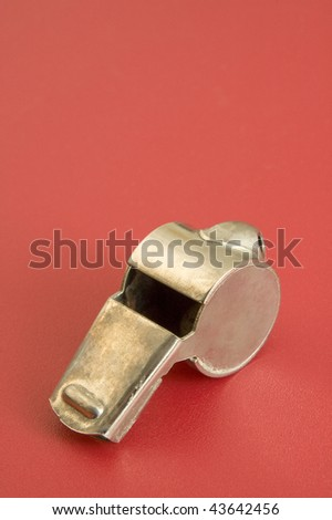 old metal whistle on red background, vertical photo