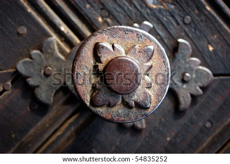 Old metallic decoration motif on a wooden door - stock photo