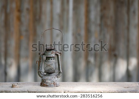 Old metallic rusty kerosene lamp with vintage background. Retro nostalgia, home decoration concept.  - stock photo