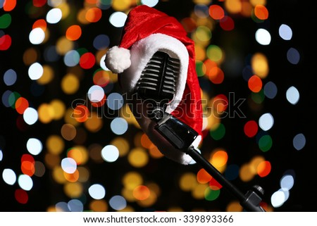 Old microphone decorated with Christmas hat against defocused lights - stock photo