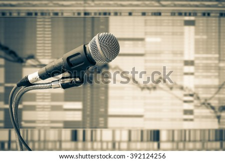 old microphone with blur image of graph stock market background
