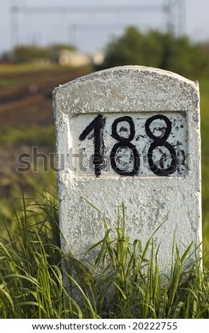 Old milestone in the grass - stock photo