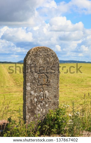 Old milestone on the side of the road - stock photo