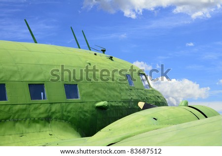 Old military aircraft detail against blue cloudy sky - stock photo