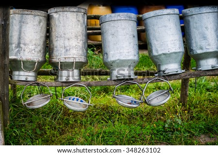 Old Milk Cans Made of Aluminum. Old milk cans made of metal to dry on a wooden stand - upside down - shallow depth of field - stock photo