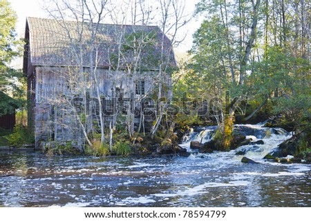 Old mill at rapids river - stock photo