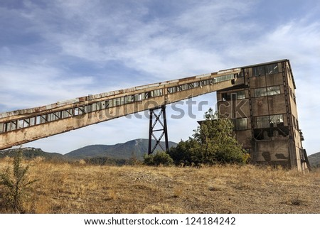 Old mines with a mine shaft tower under blue sky - stock photo