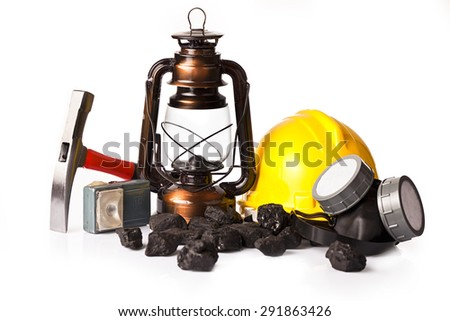 Old mining lamp with yellow helmet, electric torch, mining pickax, dust mask and loose lumps of black coal - stock photo