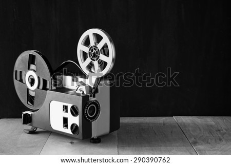 old 8mm Film Projector over wooden table and textured background - stock photo