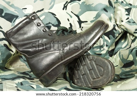 Old model high combat boots on camouflage background - stock photo