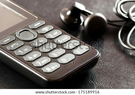 Old model of cell phone with accesories on black leather background. - stock photo