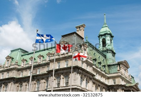 Old Montreal City Hall and flags of Quebec, Canada and the city - stock photo