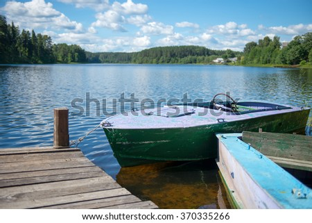 Old motor boat tied to a wooden pier on the lake - stock photo