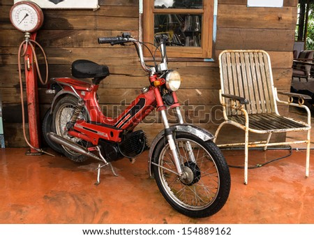 Old motorcycle and antique air pump  - stock photo