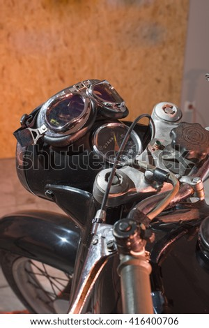 old motorcycle instrument panel with motorcycle goggles - stock photo