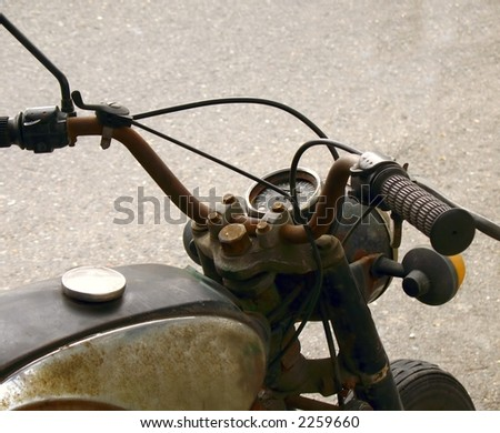 Old Motorcycle -- partial view with rusty handlebars and tank - stock photo