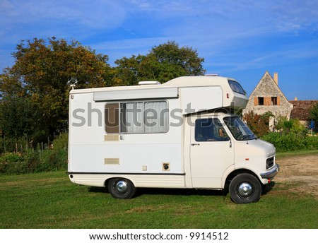 Old motorhome parked in a peaceful rural location - stock photo