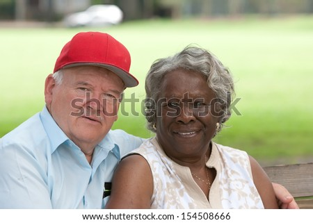 Old multiracial couple outdoors during the summer - stock photo